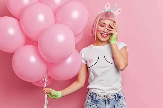 Pozytywna młoda azjatka z różowymi włosami trzyma rękę na twarzy uśmiecha się radośnie ubrana w zwykłe ubrania trzyma pęk balonów na imprezie panieńskiej