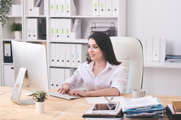 Pozytywna młoda bizneswoman siedzi przy biurku i wpisując na klawiaturze komputera podczas tworzenia wiadomości e-mail dla partnera biznesowego