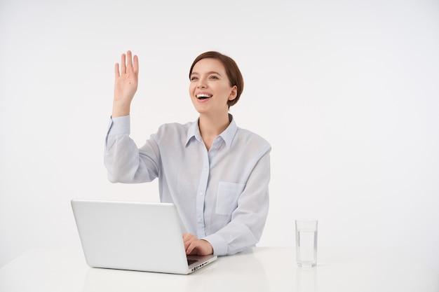 Pozytywna młoda brązowowłosa dama z naturalnym makijażem spotyka swojego kolegę i podnosi dłoń w geście powitania z szerokim, szczęśliwym uśmiechem, na białym tle
