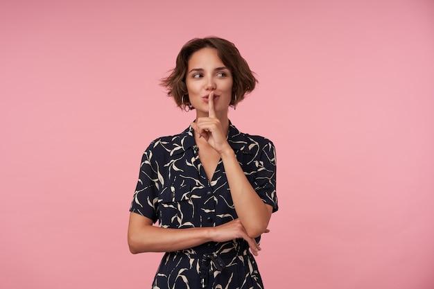 Pozytywna młoda brunetka z krótkimi fryzurami trzymająca palec wskazujący na ustach, prosząca o zachowanie tajemnicy, ubrana w czarną wzorzystą sukienkę podczas pozowania