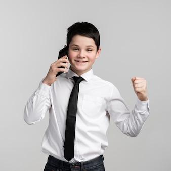 Pozytywna młoda chłopiec opowiada na telefonie komórkowym