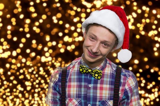 Pozytywna młoda chłopiec w santa kapeluszu. uśmiecha się europejski chłopak z muszką na koszuli. szczęśliwego nowego roku. tysiące świecących światełek w tle.