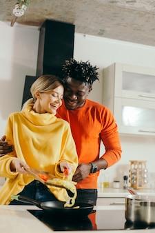 Pozytywna młoda dama stojąca z warzywami na desce do krojenia i układająca je na patelni. szczęśliwy chłopak stojący za jej plecami i uśmiechnięty