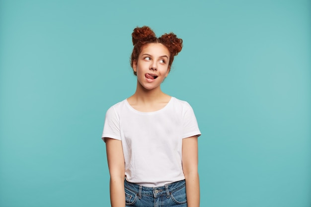 Pozytywna młoda dość kędzierzawa brunetki kobieta z kok fryzurą