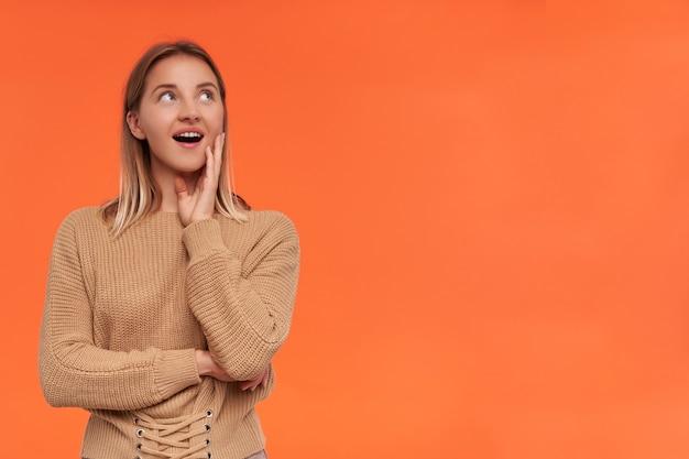 Pozytywna młoda, dość krótkowłosa blondynka z naturalnym makijażem, trzymająca podniesioną rękę na twarzy, z radością patrząc na bok, odizolowana na pomarańczowej ścianie