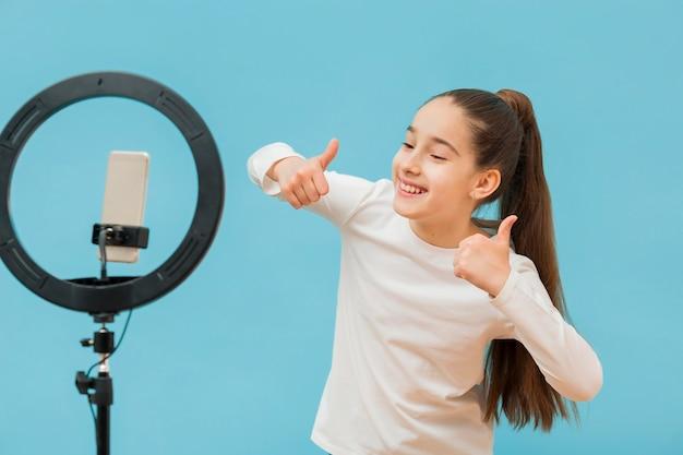 Pozytywna młoda dziewczyna nagrywa wideo na blogu