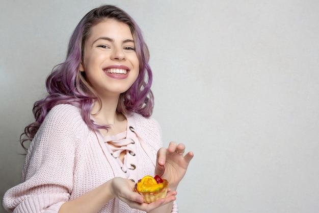 Pozytywna młoda dziewczyna z fioletowymi włosami, ciesząc się smacznym deserem z wiśni i pomarańczy. miejsce na tekst
