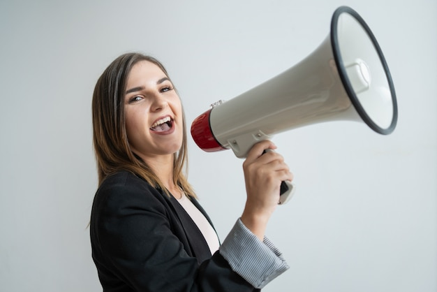 Pozytywna młoda kaukaska kobieta krzyczy w nastroszonym megafonie
