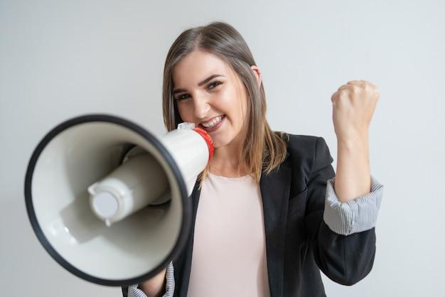 Pozytywna młoda kaukaska kobieta z megafonem pokazuje sukces
