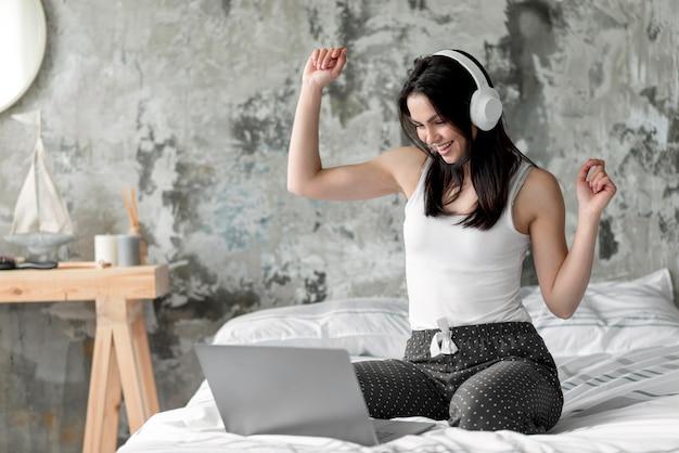 Pozytywna młoda kobieta cieszy się słuchać muzyka