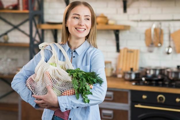 Pozytywna młoda kobieta dumna z ekologicznych artykułów spożywczych