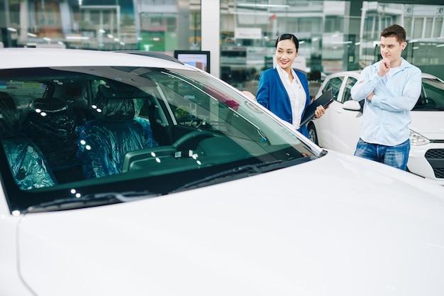 Pozytywna młoda kobieta, kierownik salonu samochodowego, zaprasza klienta na jazdę próbną
