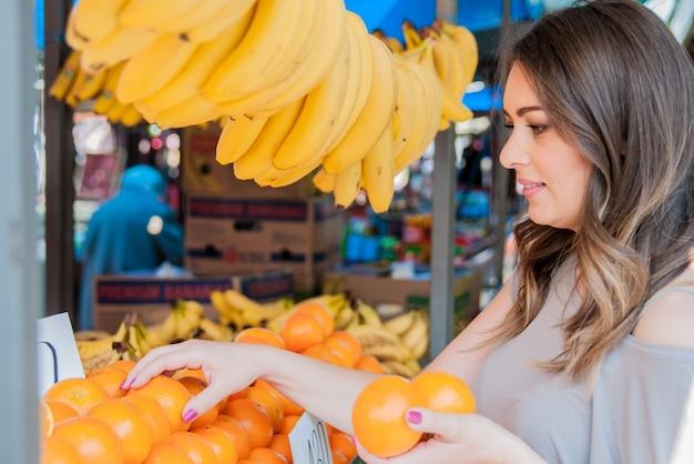 Pozytywna młoda kobieta kupuje pomarańcze na rynku. kobieta, wybierając pomarańczowy