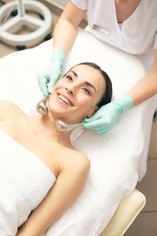 Pozytywna młoda kobieta leżąca na kanapie lekarskiej i uśmiechająca się, podczas gdy kosmetyczka trzyma krio-kije w pobliżu jej szyi