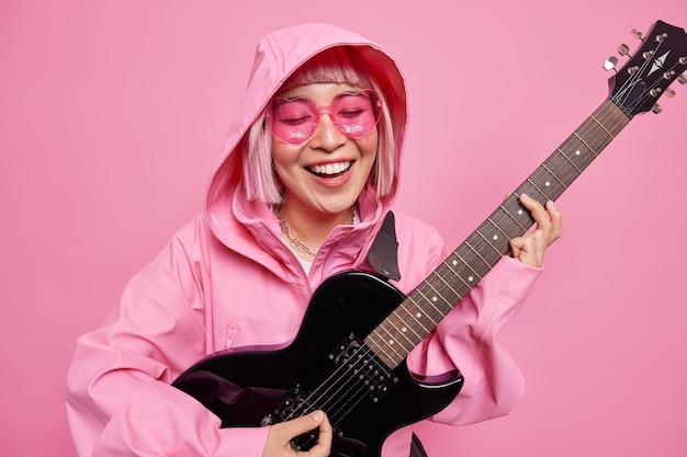 Pozytywna młoda kobieta, lubiąca muzykę, gra ulubioną muzykę, uśmiecha się na gitarze elektrycznej, szczęśliwie będąc w dobrym nastroju, nosi anorak z kapturem na głowie modne okulary przeciwsłoneczne