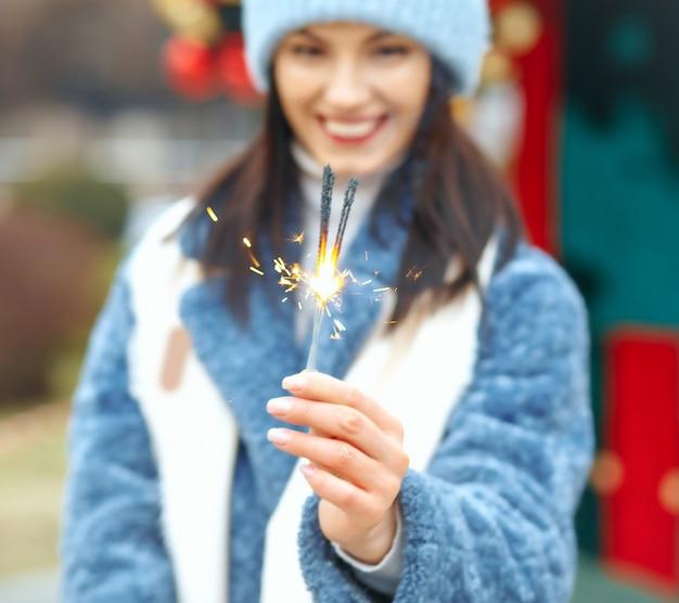 Pozytywna młoda kobieta nosi niebieski płaszcz, ciesząc się wakacjami z bengalskimi światłami