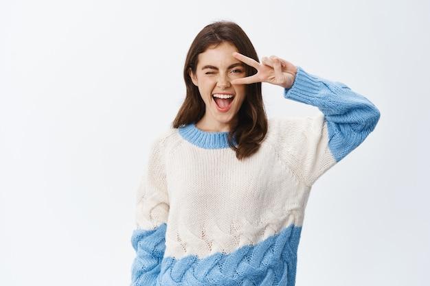 Pozytywna młoda kobieta pokazująca znak v w pobliżu oka i mrugająca z przodu, pokazując radość i szczęście, czując się optymistycznie stojąc w swetrze przy białej ścianie