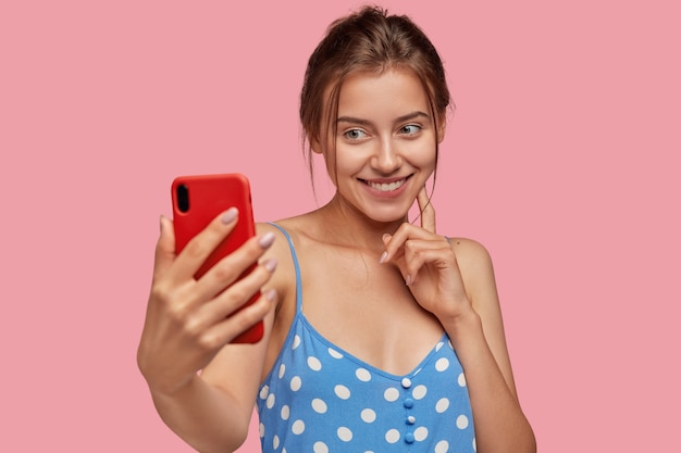 Pozytywna młoda kobieta rasy białej robi sobie zdjęcie za pomocą nowoczesnego telefonu komórkowego, ma czuły uśmiech na twarzy, ubrana jest w niebieską sukienkę w groszki, modelki na różowej ścianie. ładna pani pozuje do selfie