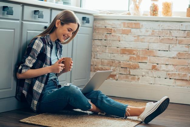 Pozytywna młoda kobieta siedzi na podłodze w kuchni z filiżanką herbaty i patrzy na ekran laptopa