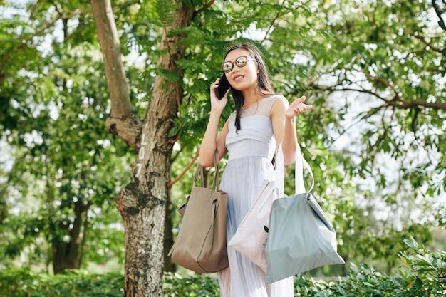 Pozytywna młoda kobieta stoi w parku z torby wielokrotnego użytku i rozmawia przez telefon z przyjacielem