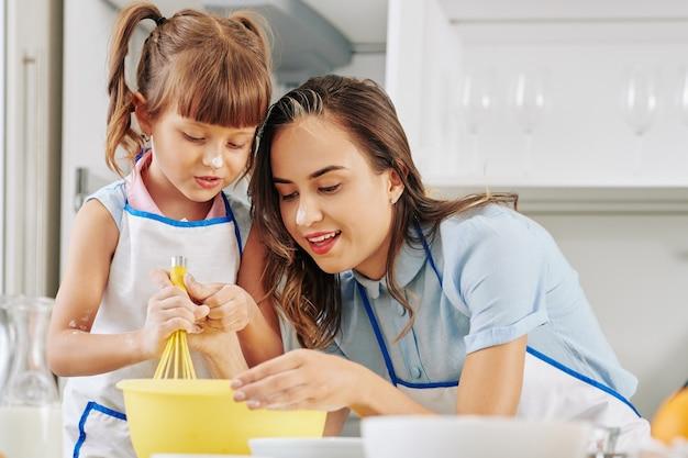 Pozytywna młoda kobieta uczy córkę, jak ubijać jajka z cukrem podczas przygotowywania lukier do ciasta