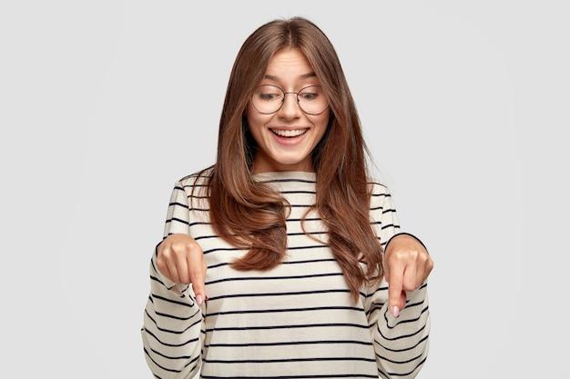 Pozytywna młoda kobieta w okularach, pozowanie na białej ścianie
