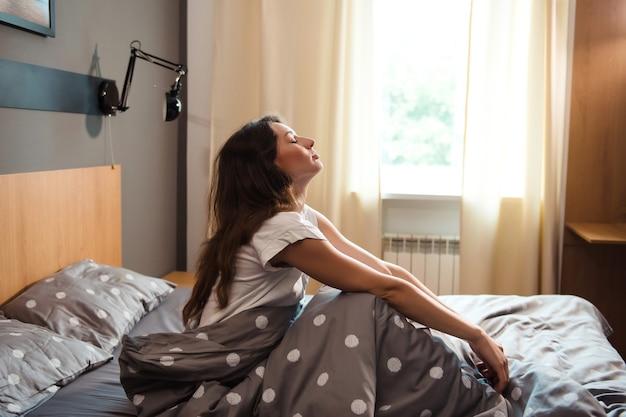 Pozytywna młoda kobieta w piżamie siedzi w łóżku i cieszy się porannym czasem w jasnej sypialni
