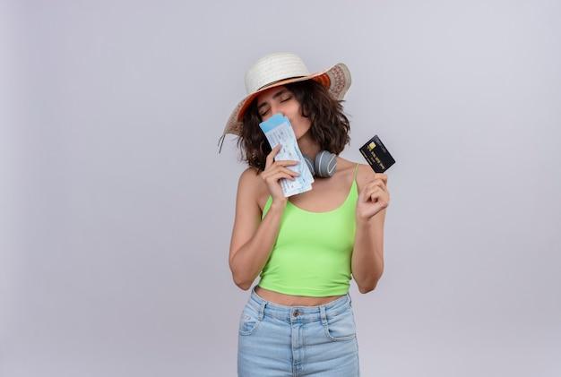 Pozytywna młoda kobieta z krótkimi włosami w zielonej bluzce w słuchawkach na sobie kapelusz przeciwsłoneczny całuje bilety lotnicze trzyma kartę kredytową na białym tle