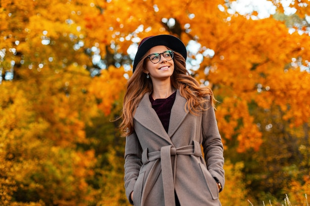 Pozytywna młoda kobieta z pięknym uśmiechem i kręconymi włosami w eleganckiej czapce w stylowym płaszczu w modnych okularach cieszy się weekendem w jesiennym parku. ładny szczęśliwy hipster dziewczyna relaksuje się na zewnątrz.