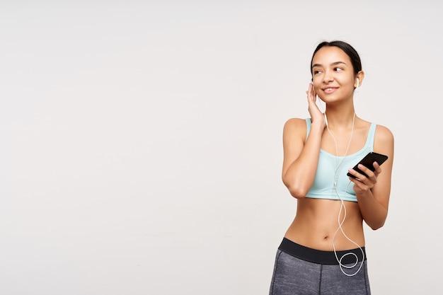 Pozytywna młoda ładna brązowowłosa kobieta z przypadkową fryzurą, uśmiechnięta lekko podczas słuchania muzyki przez słuchawki i telefon komórkowy, odizolowana na białej ścianie w sportowym ubraniu