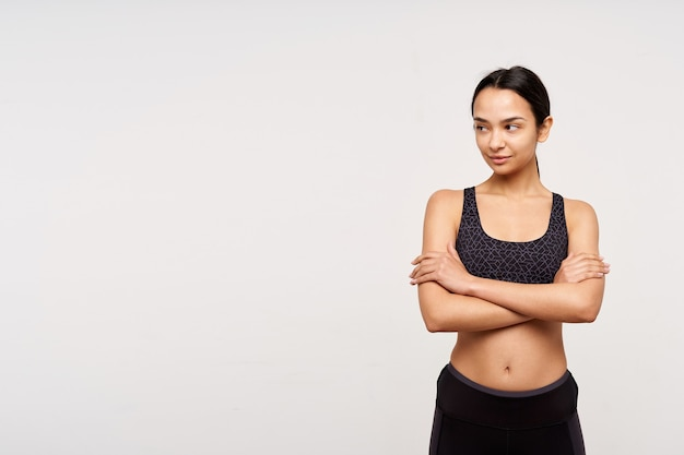 Pozytywna młoda, ładna ciemnowłosa sportowa dama trzymająca ręce skrzyżowane, patrząc na bok w zamyśleniu, stojąca nad białą ścianą w sportowym ubraniu
