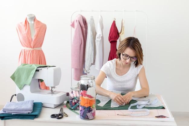 Pozytywna młoda ładna dziewczyna projektant krawcowa pracuje nad nowym projektem, siedząc przy biurku z maszyną do szycia w swoim warsztacie. kreatywna koncepcja biznesowa.