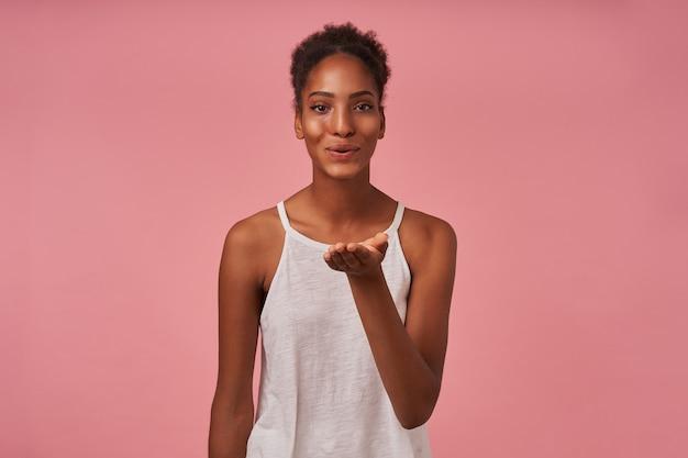 Pozytywna młoda, ładnie kręcona brunettened kobieta trzymająca dłoń uniesioną i dmuchająca radośnie pocałunek do przodu, odizolowana na różowej ścianie
