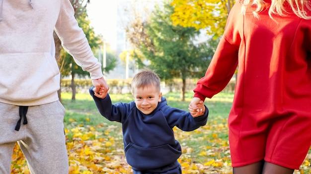 Pozytywna młoda matka i ojciec podnoszą uroczego chłopca trzymającego się za ręce syna spacerującego wzdłuż słonecznego jesiennego parku miejskiego w miły ciepły dzień zbliżenie