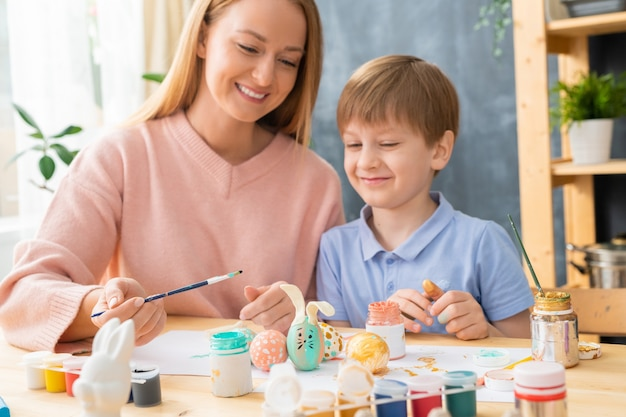 Pozytywna młoda matka siedzi przy stole i robi projekt królika na pisanki ze swoim synem