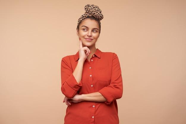 Pozytywna młoda piękna brunetka kobieta z naturalnym makijażem, uśmiechnięta przyjemnie, rozmarzona i trzymająca palec wskazujący na policzku, stojąca nad beżową ścianą