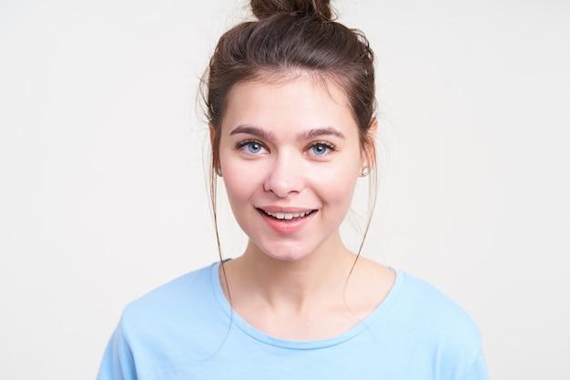 Pozytywna młoda piękna niebieskooka brunetka kobieta z naturalnym makijażem uśmiecha się lekko, patrząc z radością przed siebie, stojąc nad białą ścianą