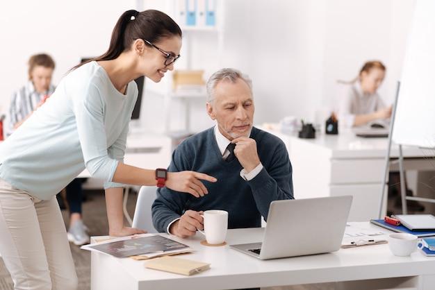 Pozytywna młoda pracownica nosząca inteligentne zegarki, opierając lewą rękę na stole, wskazując na komputer