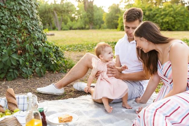Pozytywna młoda rodzina z małą córeczką spędzającą razem czas