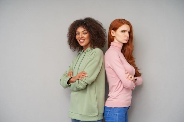 Pozytywna młoda śliczna brązowowłosa ciemnoskóra kobieta w zielonej bluzie z kapturem uśmiechająca się przyjemnie, pozując na szarej ścianie ze smutnym, długowłosym przyjacielem