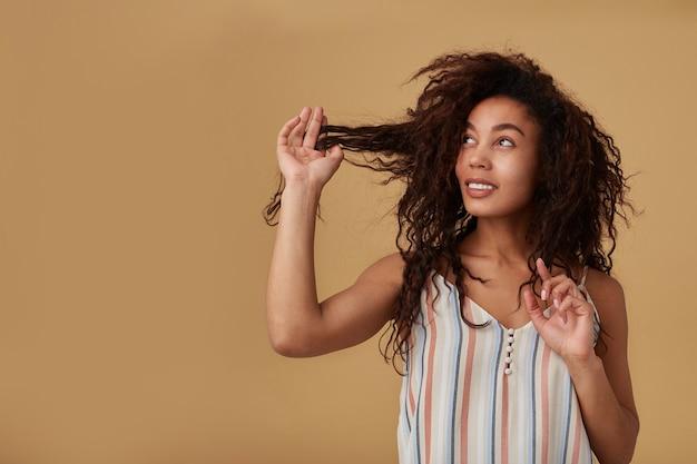 Pozytywna młoda śliczna ciemnoskóra brunetka kobieta ciągnie swoje długie kręcone włosy z uniesioną ręką i patrzy wesoło na bok, odizolowana na beżu