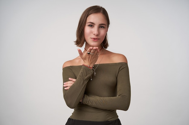 Pozytywna młoda śliczna ciemnowłosa dama z krótką fryzurą, która trzyma dłoń uniesioną do góry, dmuchając pocałunkiem do przodu, ubrana w oliwkową bluzkę, stojąc na białej ścianie