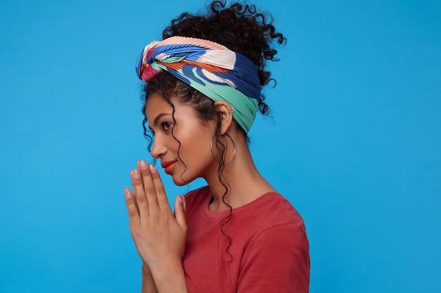 Pozytywna młoda śliczna ciemnowłosa, kręcona kobieta z wielokolorową opaską, lekko uśmiechnięta, unosząca ręce w geście modlitwy, stojąca nad niebieską ścianą