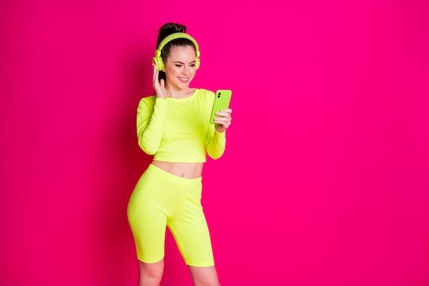 Pozytywna młoda sportsmenka używa smartfona słuchania zestawu słuchawkowego playlisty nosić żółte spodenki izolowane na różowym jasnym tle koloru