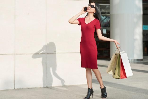 Pozytywna moda azjatycka dziewczyna w okularach przeciwsłonecznych i czerwonej sukience, trzymając torby na zakupy i rozmawiając przez telefon na zewnątrz