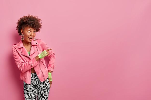 Pozytywna, modna, kręcona kobieta wskazuje palcem wskazującym na puste miejsce, pokazuje baner promocyjny, poleca, kieruje do klubu sportowego, wskazuje niesamowite miejsce