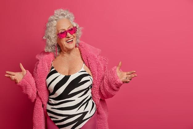 Pozytywna modna starsza kobieta rozkłada dłonie jest w radosnym nastroju