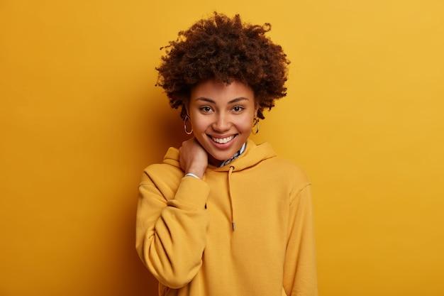 Pozytywna nastolatka uśmiecha się radośnie, dotyka szyi