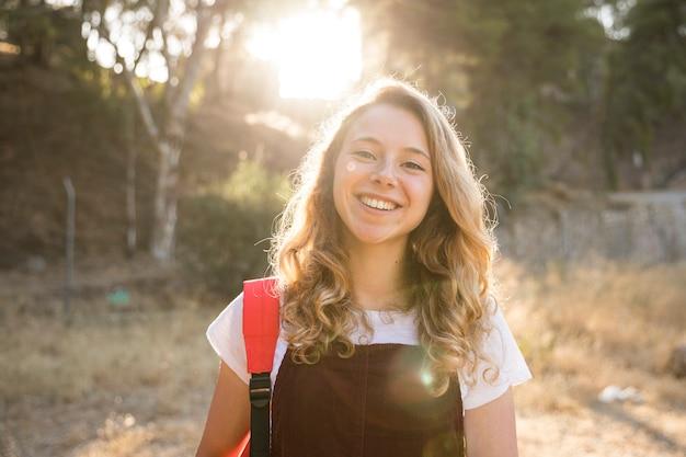 Pozytywna nastoletnia dziewczyna ono uśmiecha się w naturze