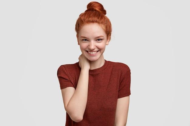 Pozytywna nieśmiała rudowłosa dziewczyna ma czuły uśmiech, trzyma rękę na szyi, jest w dobrym nastroju